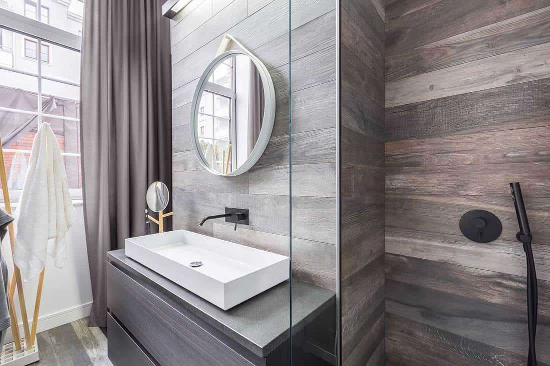 Modern bathroom interior with walk in shower, wooden walls, white countertop basin and round mirror on white frame
