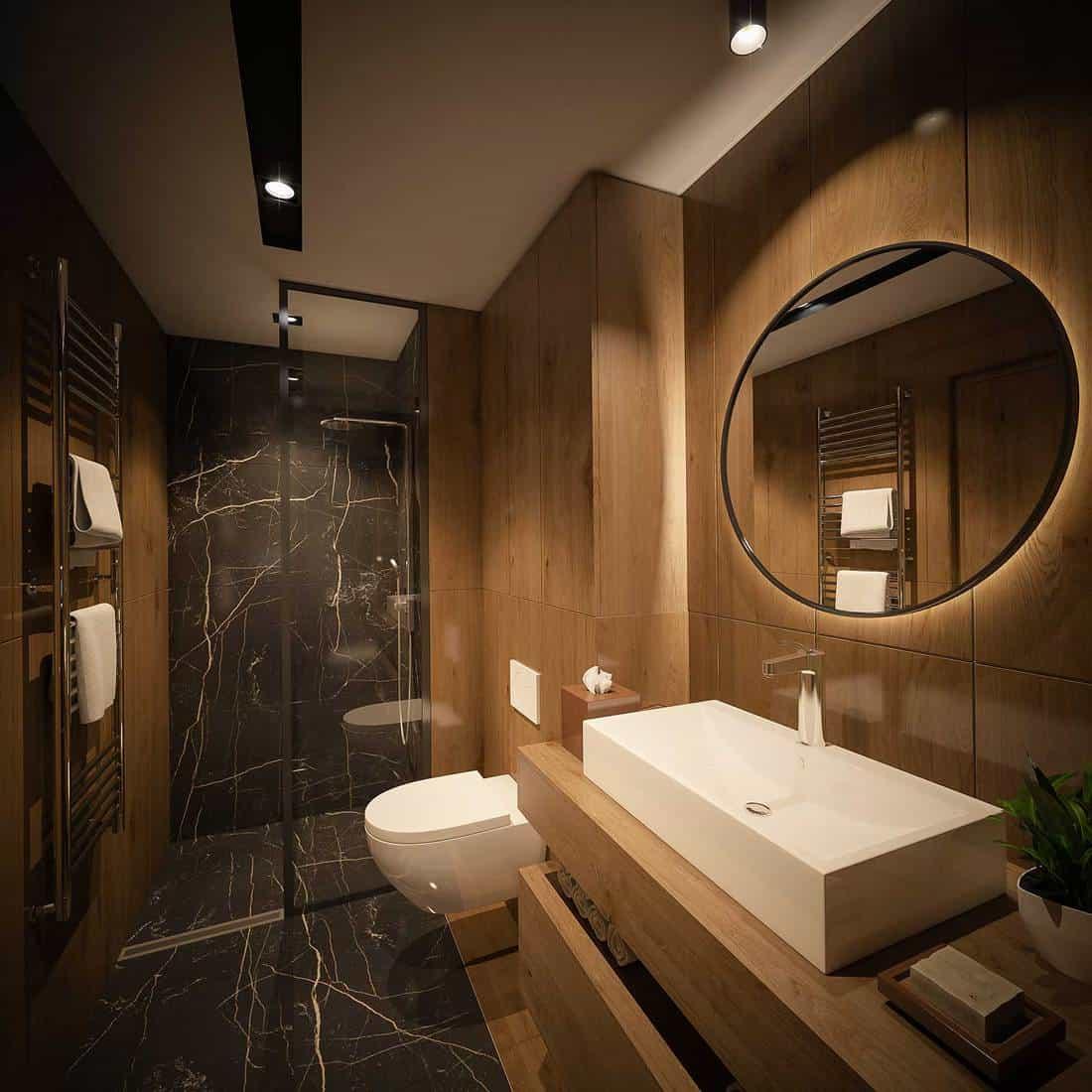 Modern bathroom interior with wooden walls, ceramic sink, round mirror, shower and toilet