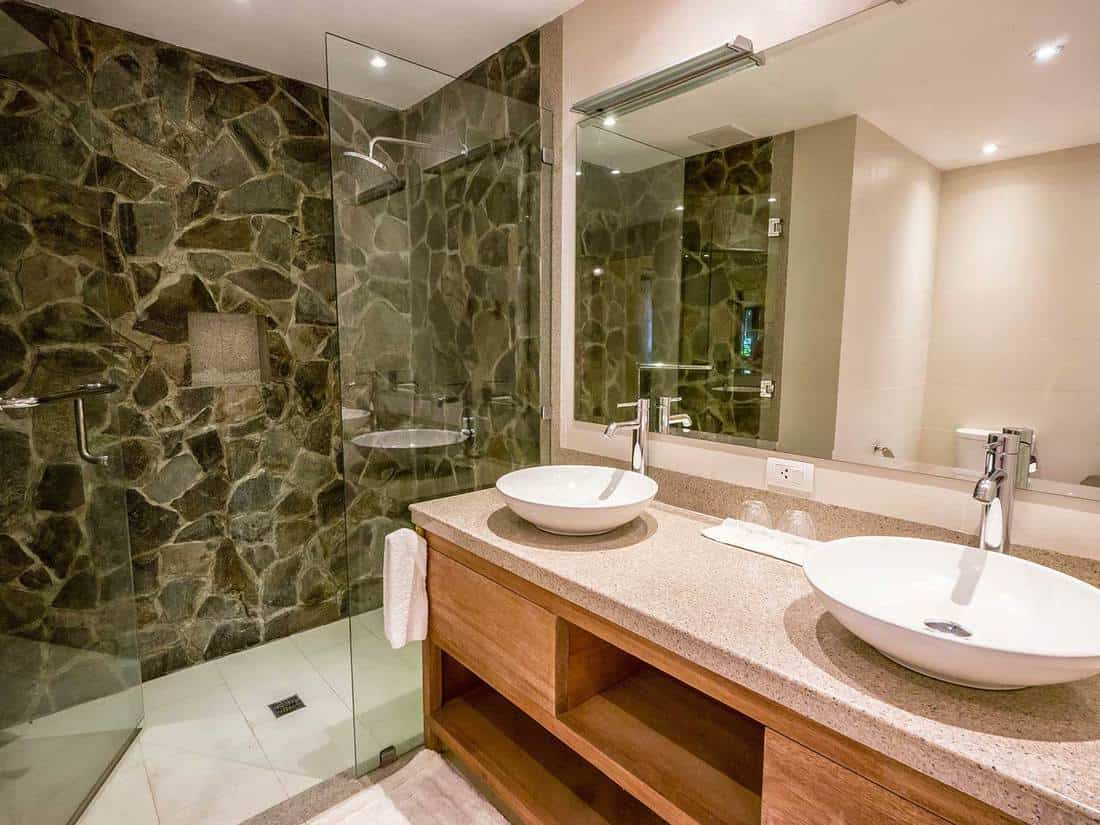 Modern bathroom with double ceramic sinks on and single-hole chrome faucets on granite counter tops