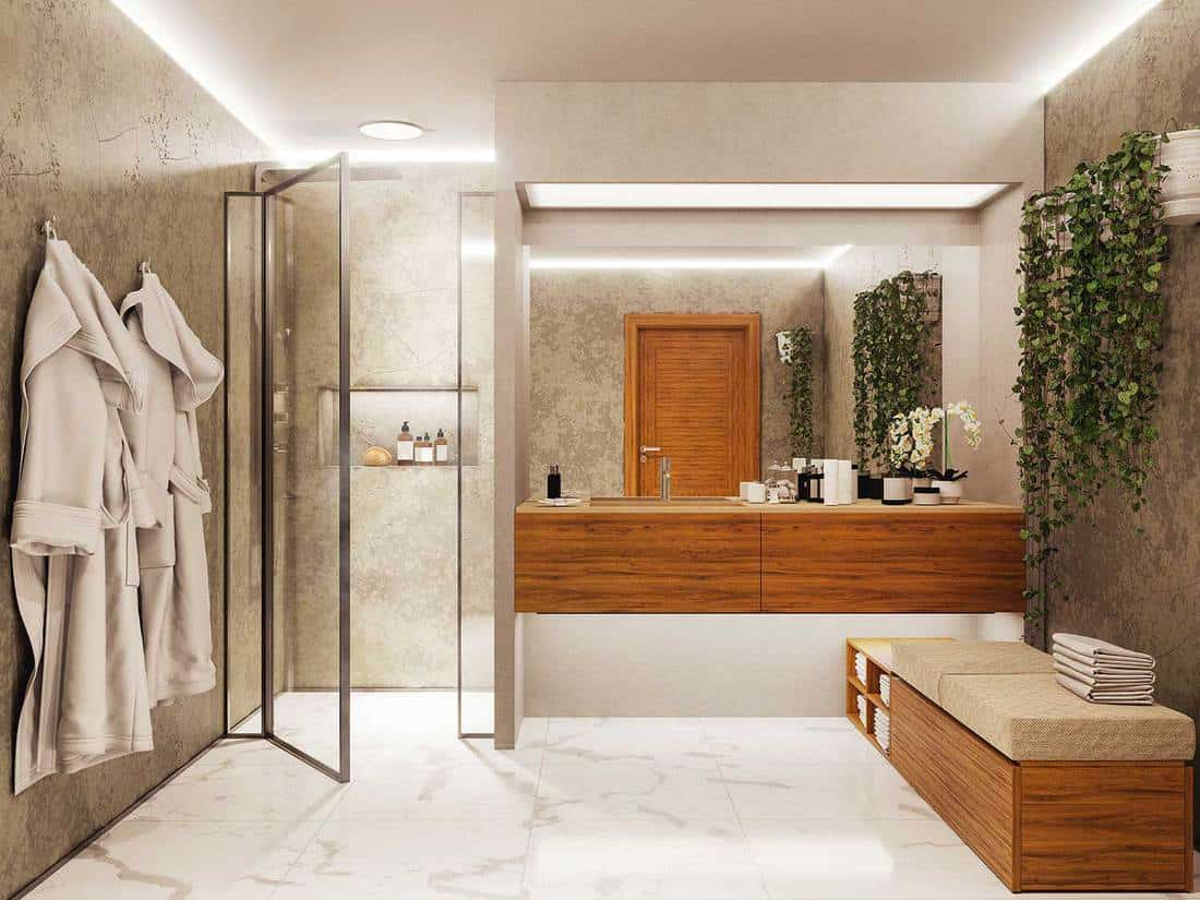Modern bathroom with glass shower, botanic elements, rough concrete and wooden sink
