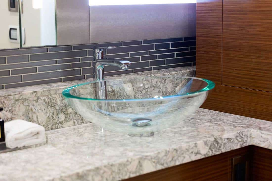 Modern bathroom with glass wash basin and marble countertop