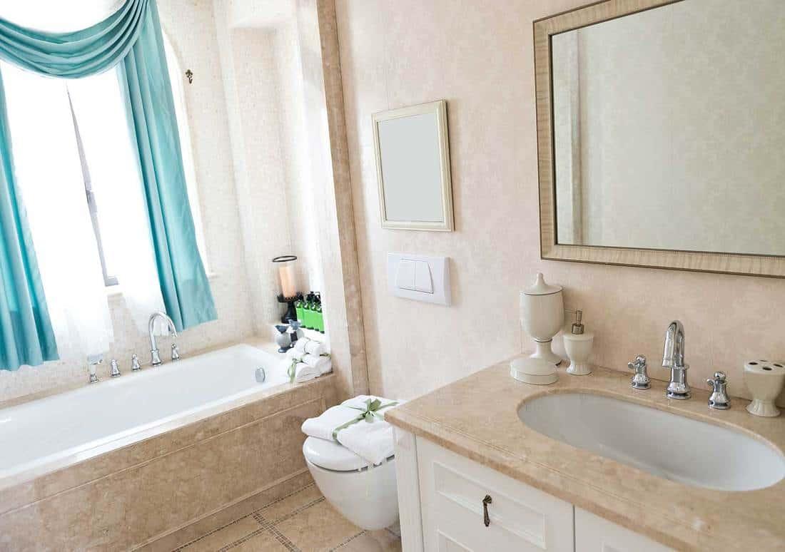 Modern bathroom with mirror, sink, bathtub and teal curtains