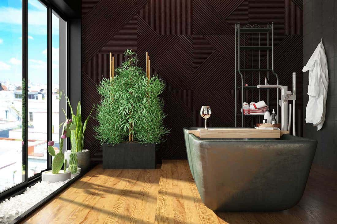 Modern bathroom with plants, parquet floor and city view window