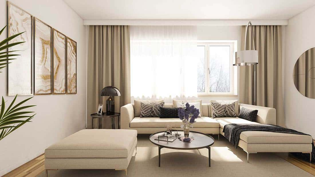 Modern beige living room interior with wall decorations, round mirror and window on a sunny day
