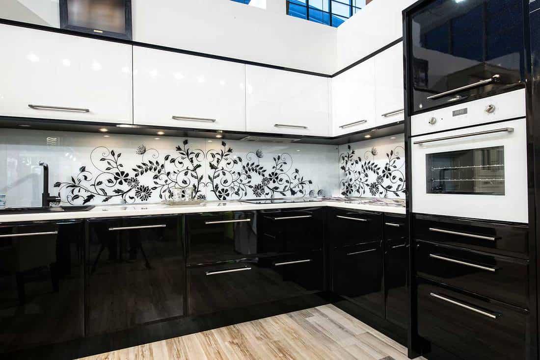 Modern black and white kitchen interior with parquet floor