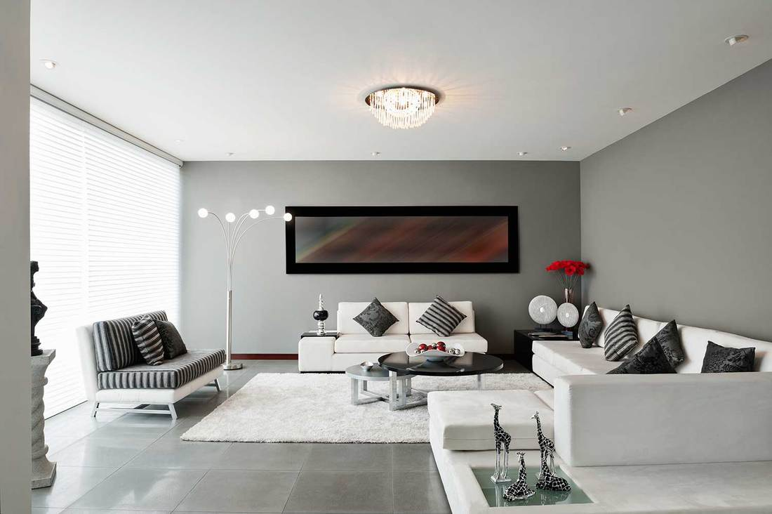 Modern black and white themed living room with cozy white carpet on grey tiled floor