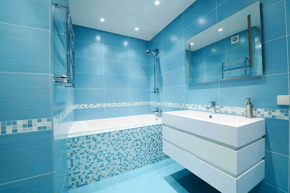 Modern blue bathroom interior with mosaic design tiles, mirror and large white sink