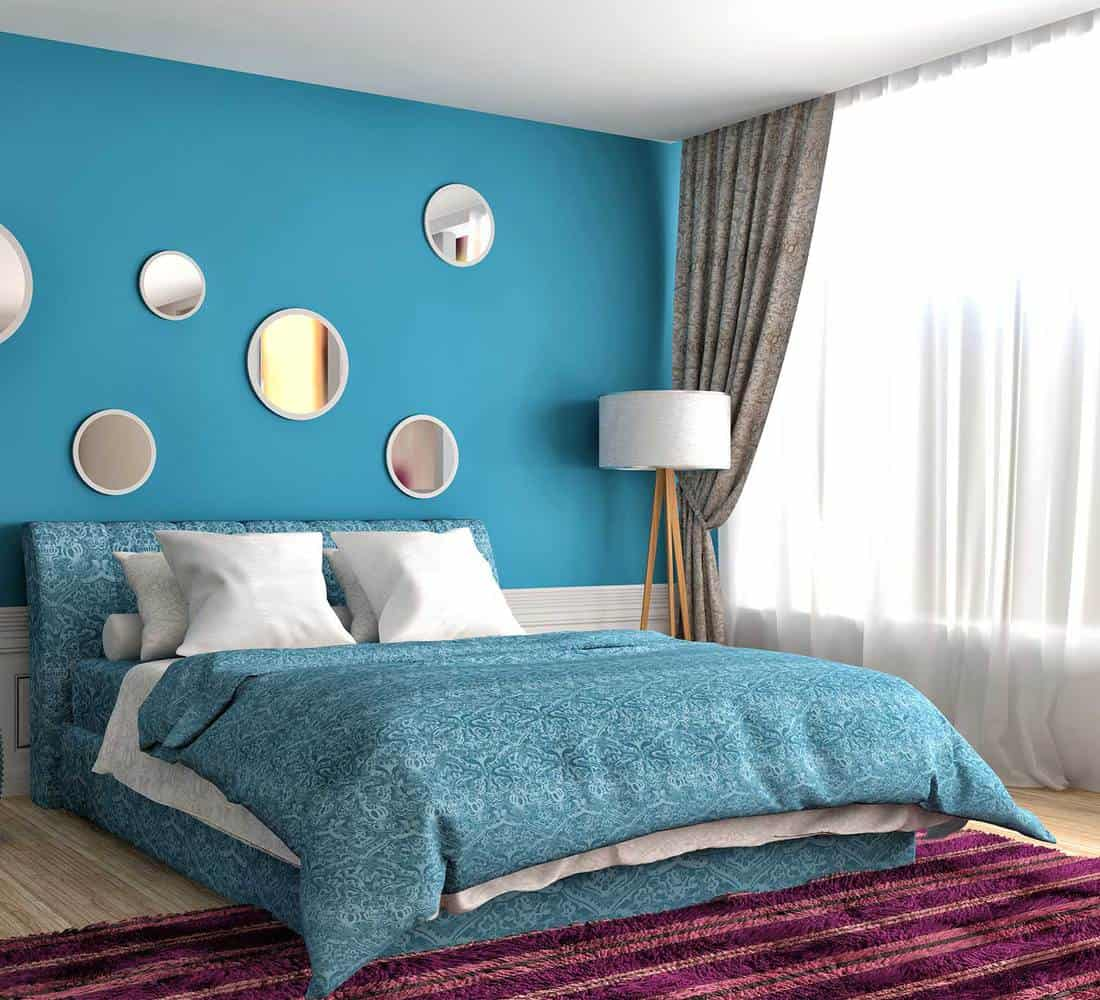 Modern blue bedroom with purple carpet, lamp and round silver wall decor