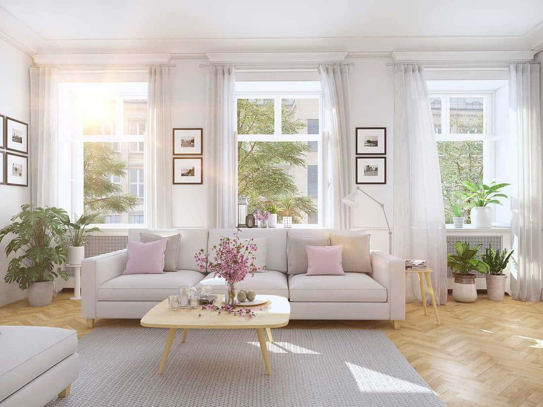 Modern bright living room with white curtain window, sofa, coffee table, house plants and parquet floor
