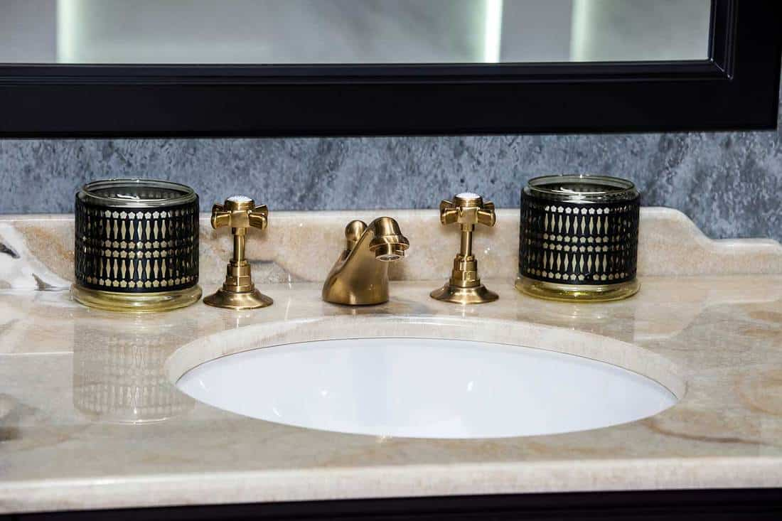 Modern brown ceramic sink with golden faucet