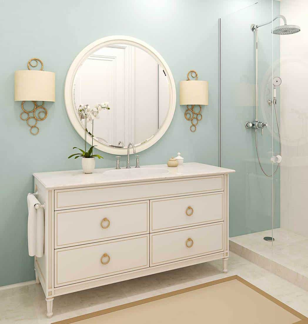 Modern classic style bathroom interior with shower, big round mirror and white cabinet