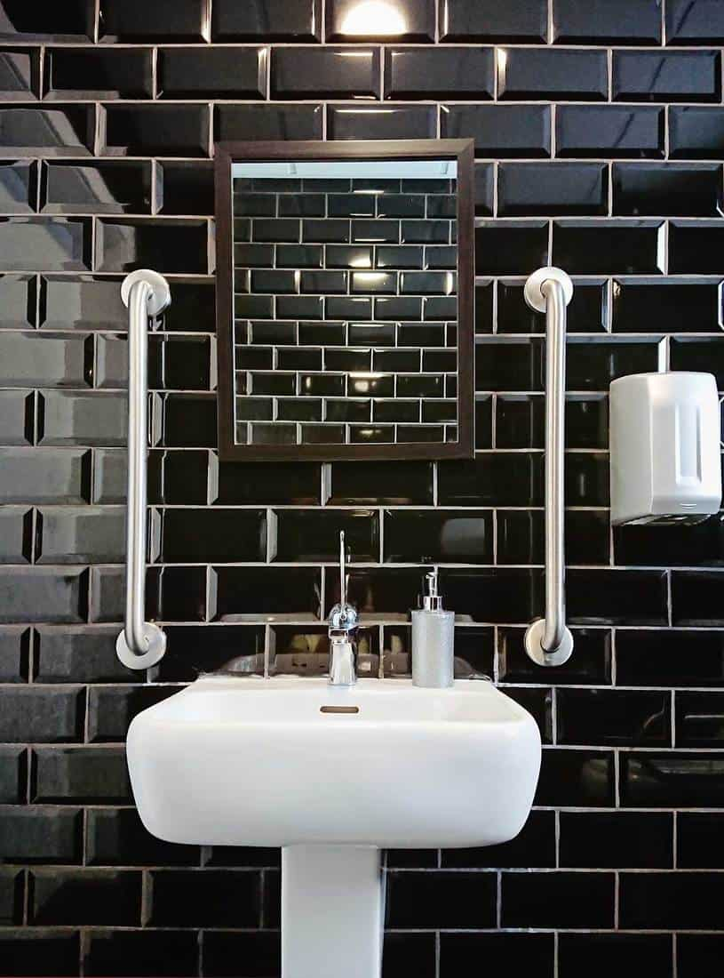 Modern design of toilet closet room with black glossy tiles