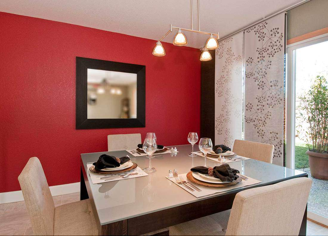 Modern dining room with glass top table, red wall with mirror, place settings, window shades and overhead lighting