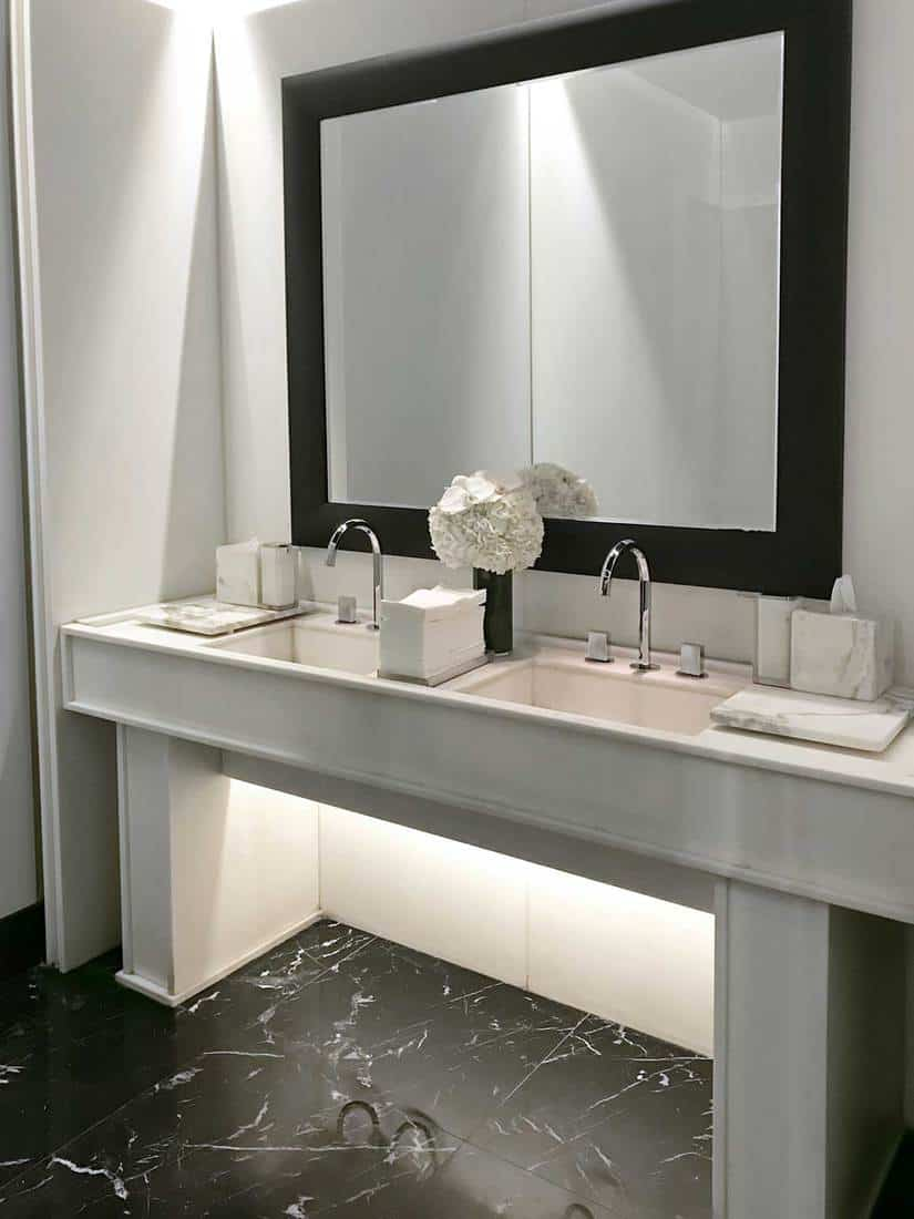 Modern female public restroom with double sinks and large mirror