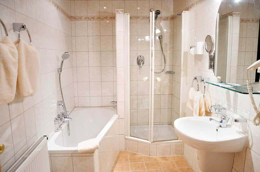 Modern fully tiled hotel bathroom with bath tub, shower, sink, towels, large and cosmetic mirror