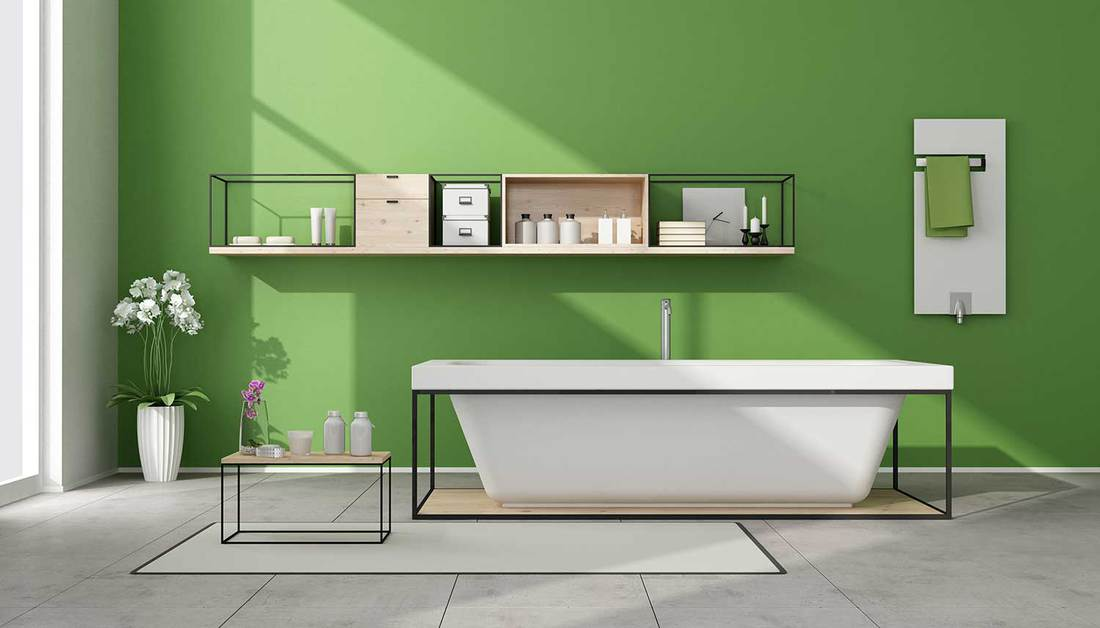 Modern green bathroom interior with bathtub, sideboard and white heater