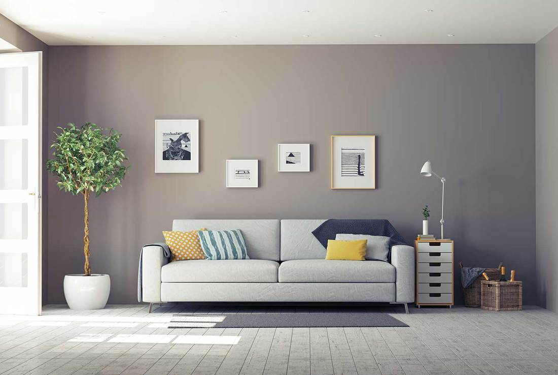 Modern gray themed living room interior with cozy sofa, wall art decor and hardwood floor