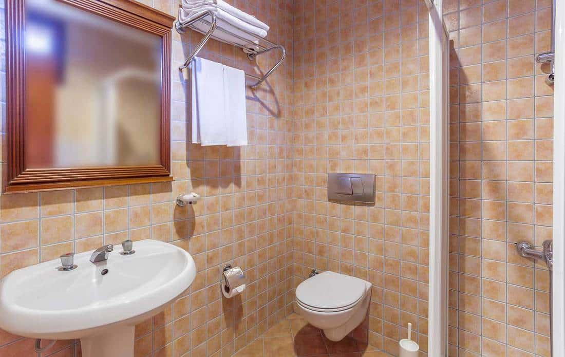 Modern hotel bathroom interior with sink, toilet, shower and mirror