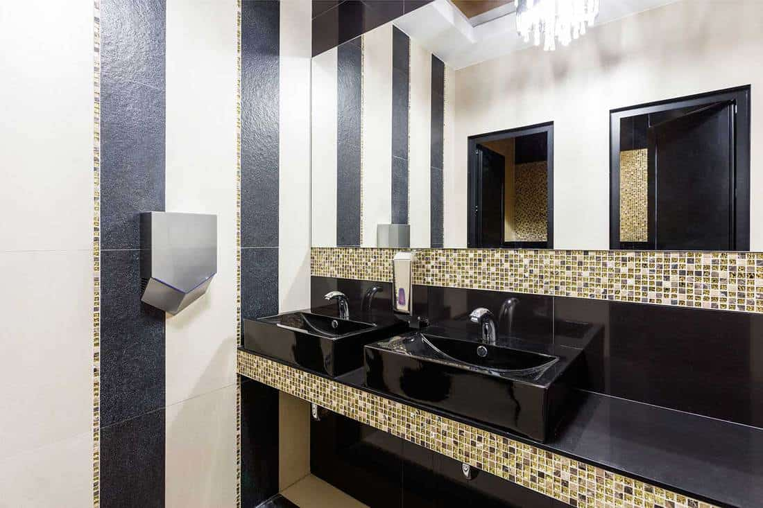 Modern hotel restroom with double sink in dark colors and mosaic design