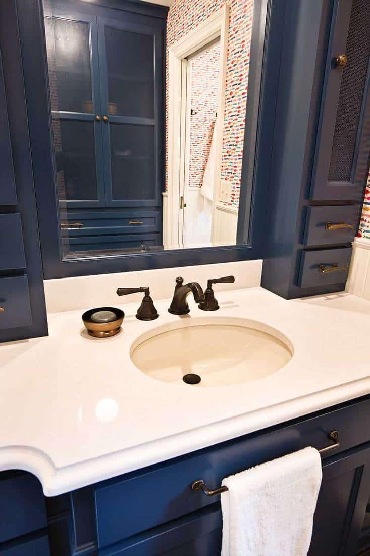 Modern house bathroom sink with dark blue wooden cabinets