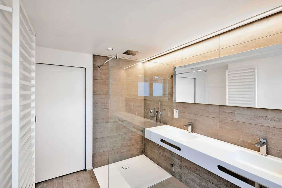 Modern house bathroom with two faucets on large white sink, glass shower and mirror