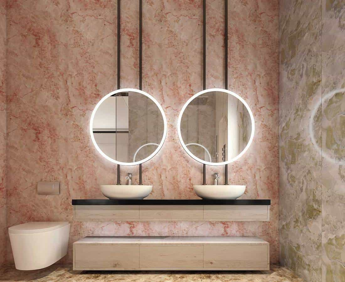 Modern interior design of bathroom vanity with all walls made of stone slabs with circle mirrors, minimalist and clean concept