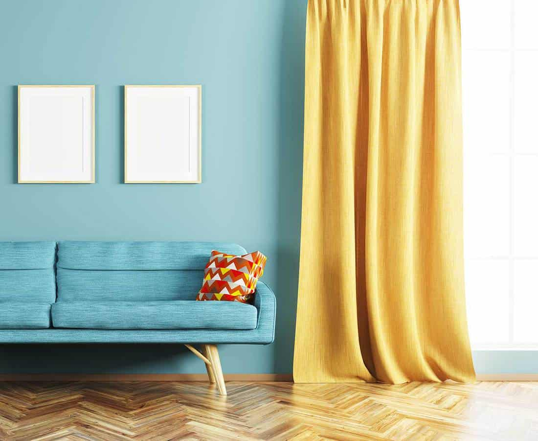 Modern interior design of living room with blue wall and sofa, frames and window with yellow curtain