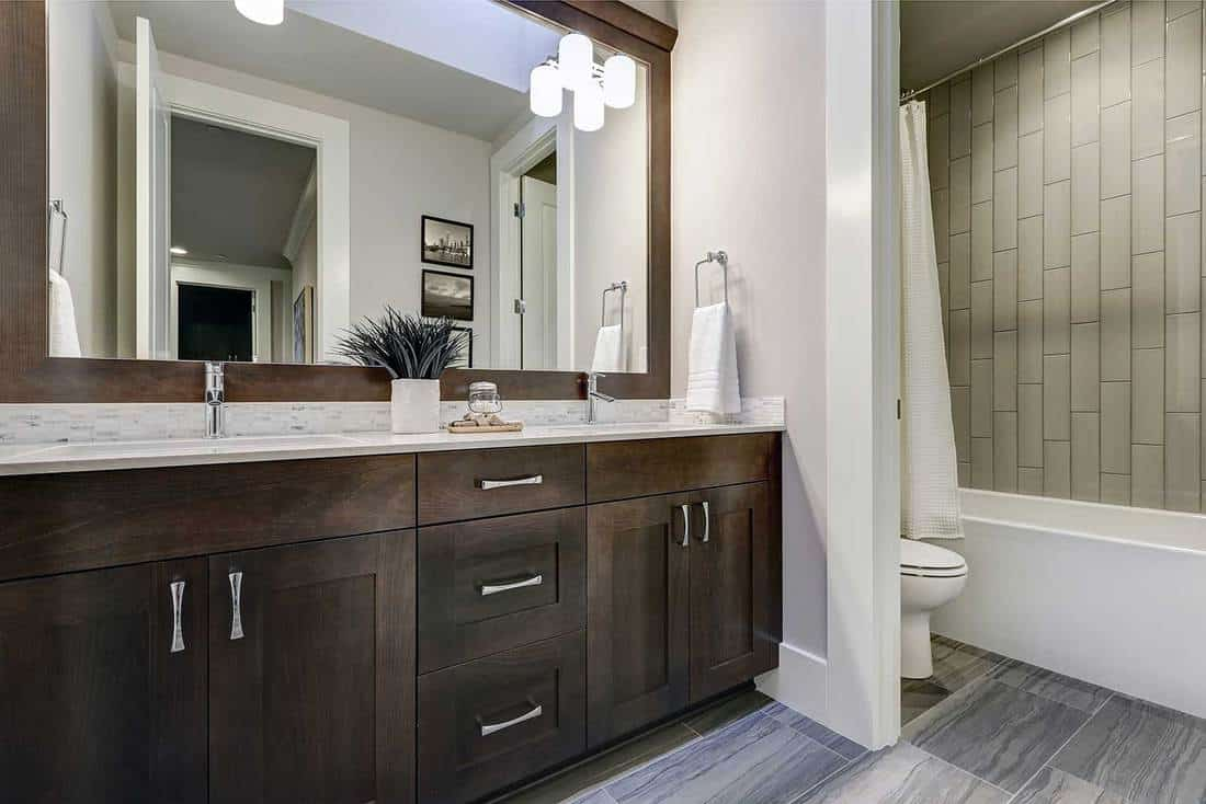 Modern interior house bathroom with dark wood cabinets, large mirror, bathtub and toilet