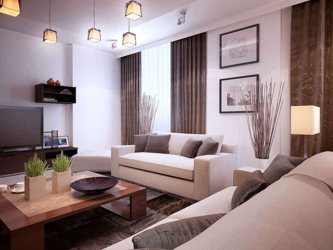 Modern living room interior with sofa, wooden coffee table, tv and pictures on white wall