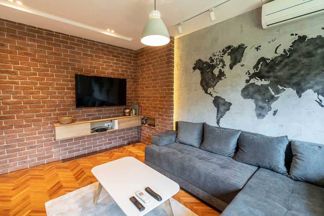 Modern living room interior with world map on the wall, cozy grey sofa, parquet floor and TV hang on brick wall