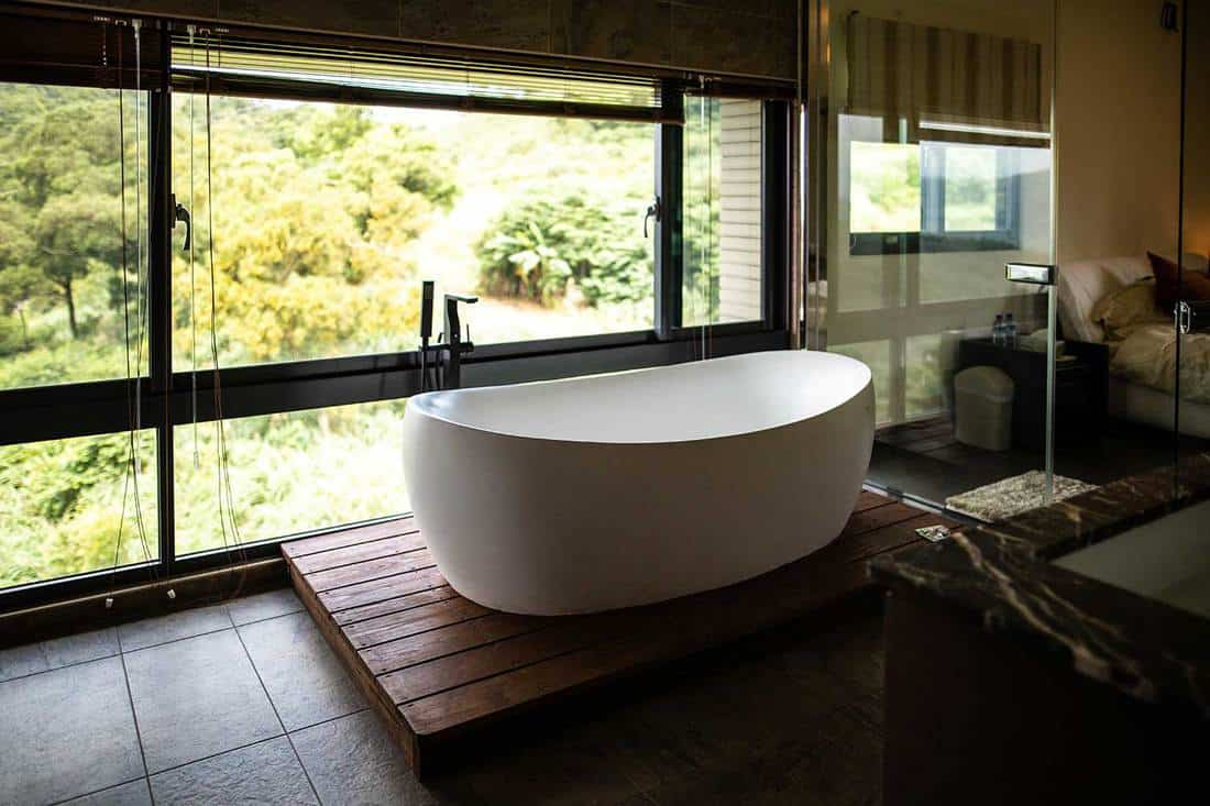 Modern luxury hotel bathroom with white bathtub near large window with nature view