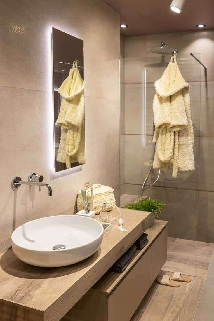 Modern scandinavian style bathroom in neutral tones with shower and large rounded basin on a wooden cabinet