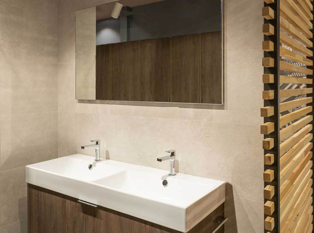 Modern scandinavian style restroom with a large mirror above two white sinks
