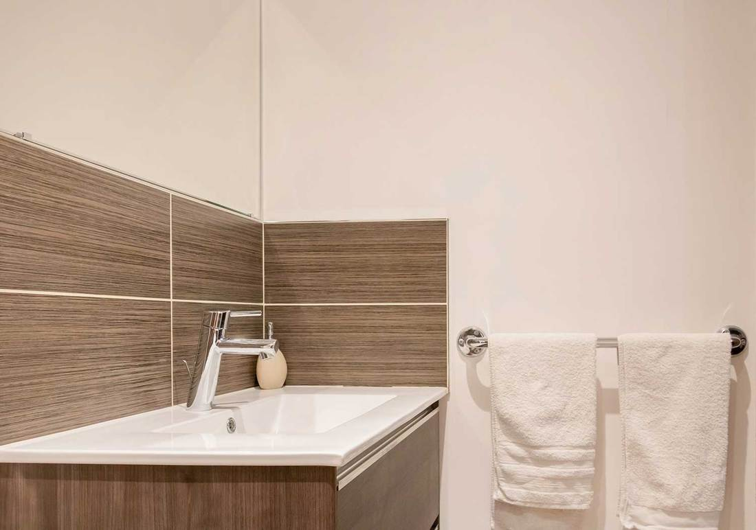 Modern sink in a bathroom with brown wall tiles
