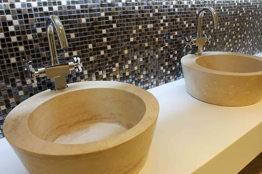 Modern sinks in a restroom with mosaic design wall