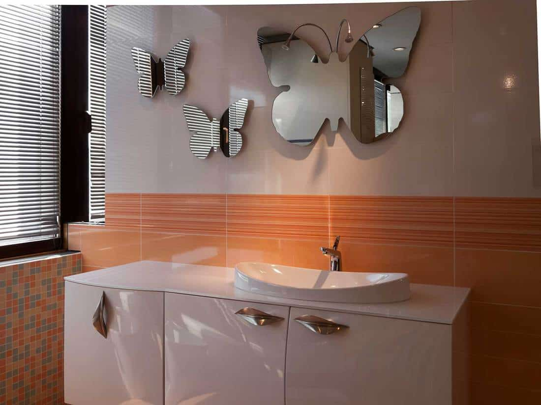 Modern style bathroom design with butterfly shaped mirrors and orange tiles