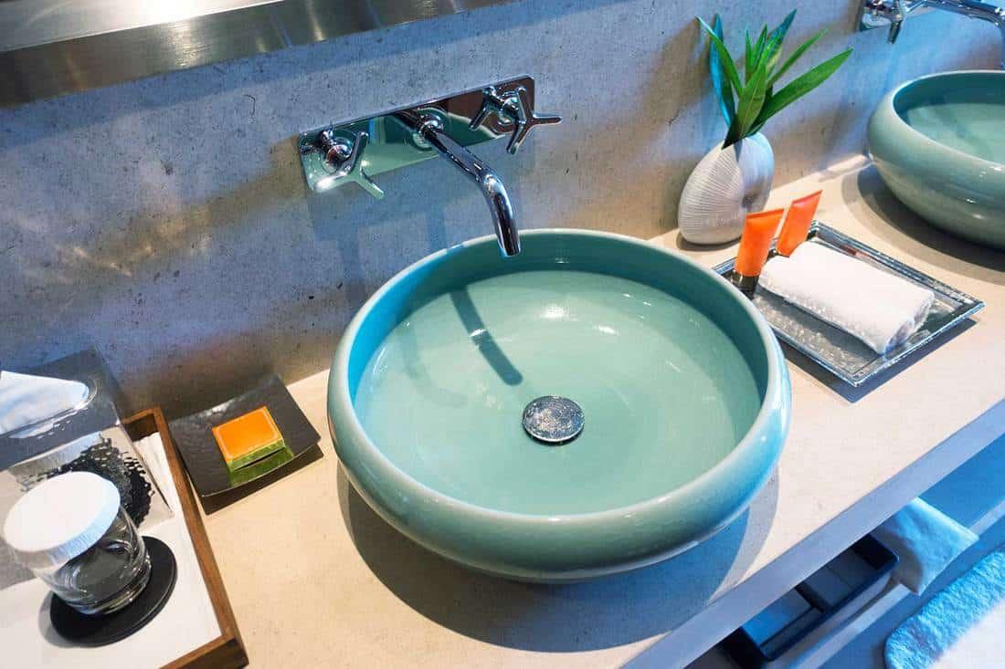 Modern teal bathroom sinks in a public restroom