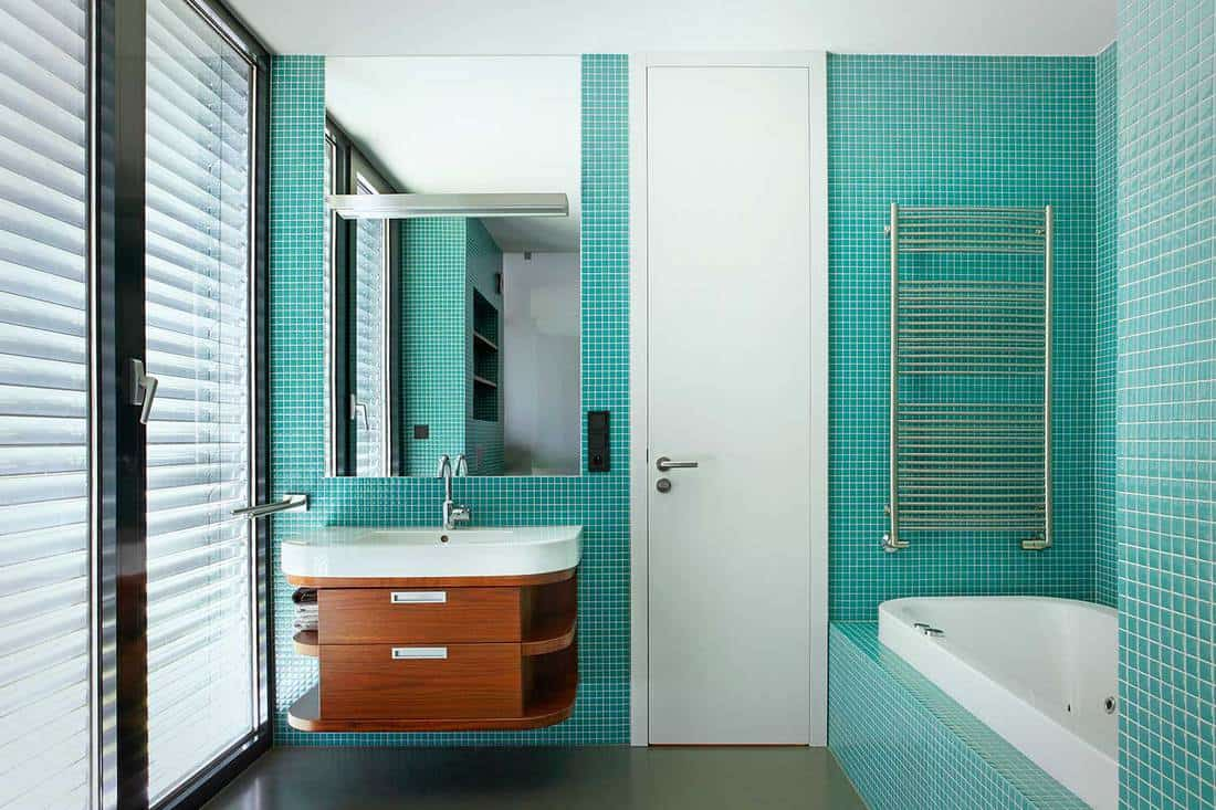 Modern teal themed bathroom interior with wash basin, mirror and bathtub