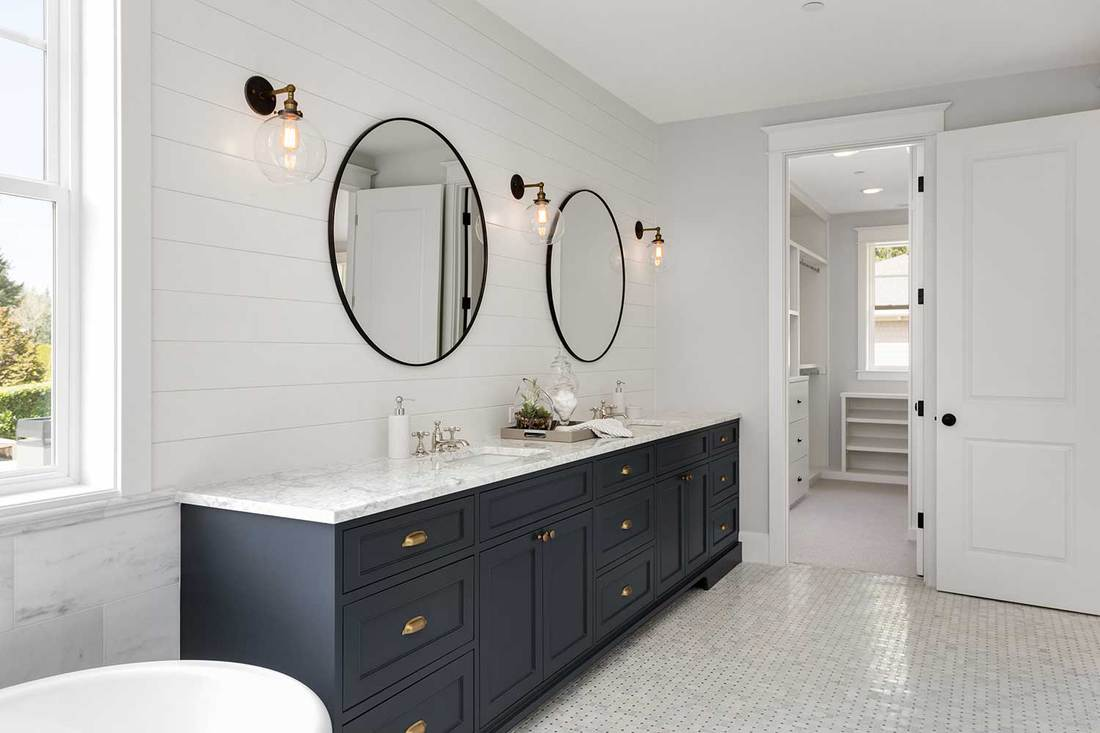 Modern white bathroom in new home with two sinks and two large mirrors
