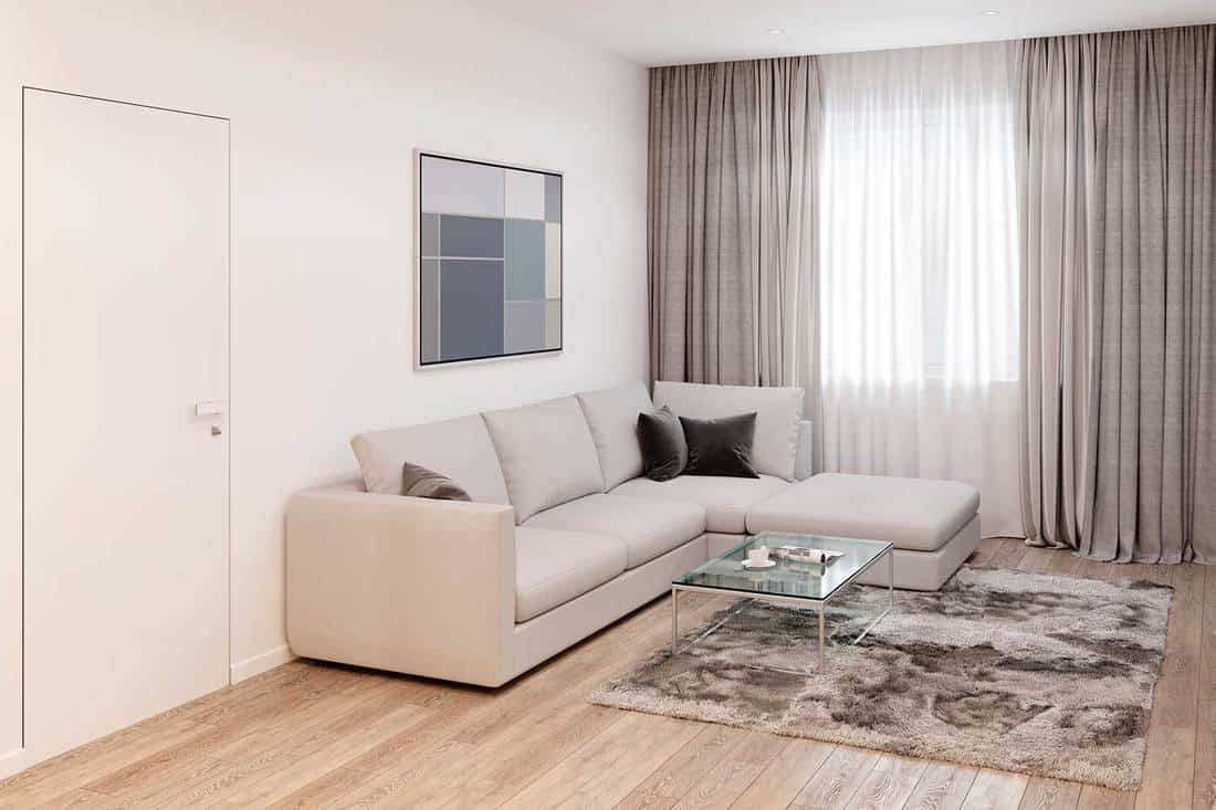 Modern white living room with sofa, coffee table, picture on wall and parquet flooring