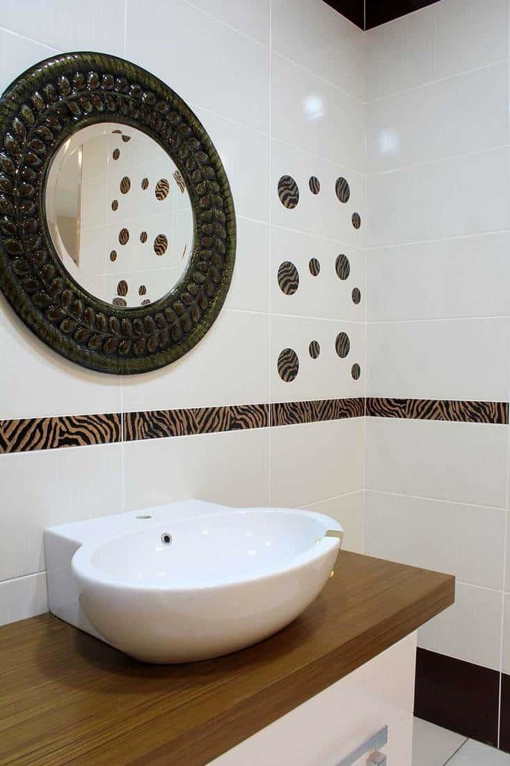 Modern white sink in a house bathroom with round mirror