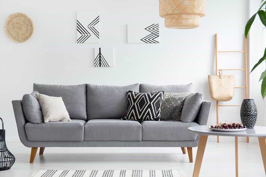 Pillows on gray sofa in white living room interior with posters, lamp and coffee table