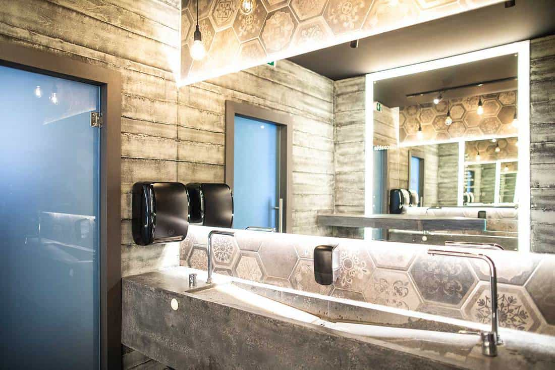 Public restroom with mirrors, stone countertop and wooden walls