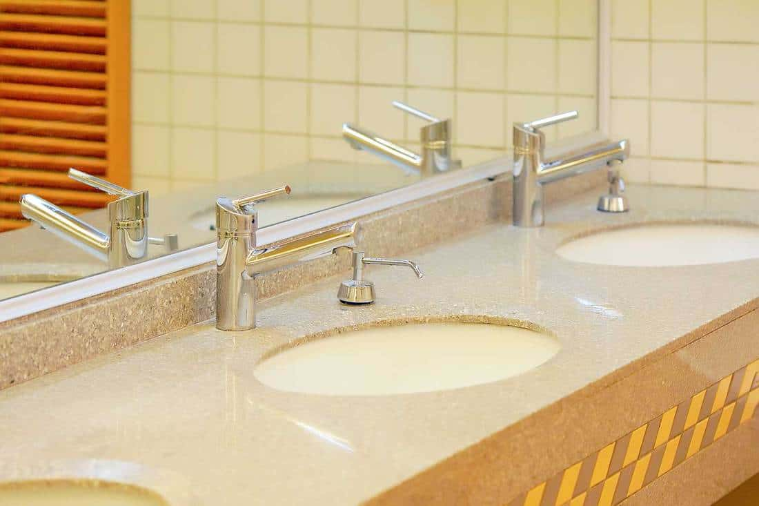 Public restroom with modern design sink and stainless steel faucet
