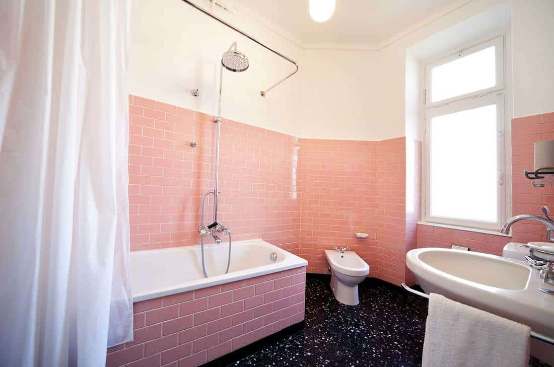 Retro style apartment bathroom with pink brick wall tiles