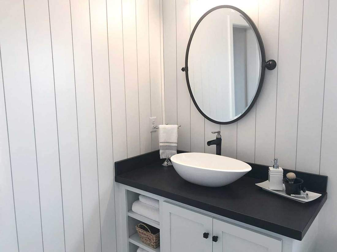 Round mirror above white ceramic sink on white cabinet with black countertop