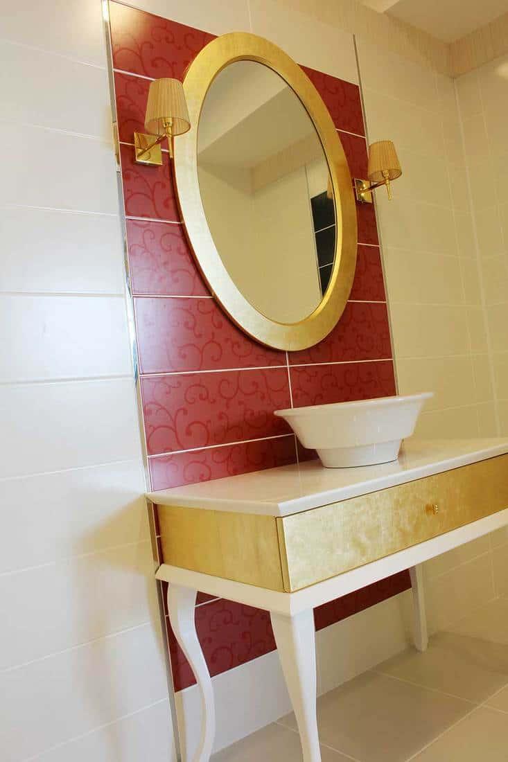 Round mirror on modern bathroom sink in a luxury home
