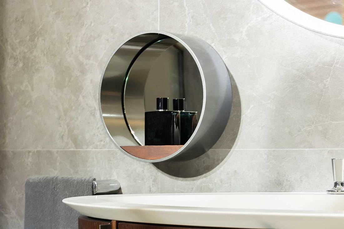 Round mirror with a bottle of perfume for men above the sink basin of a modern bathroom