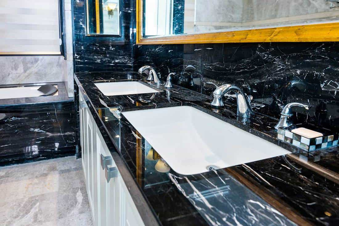 Sink and bathtub with dark marble tiles in modern bathroom interior