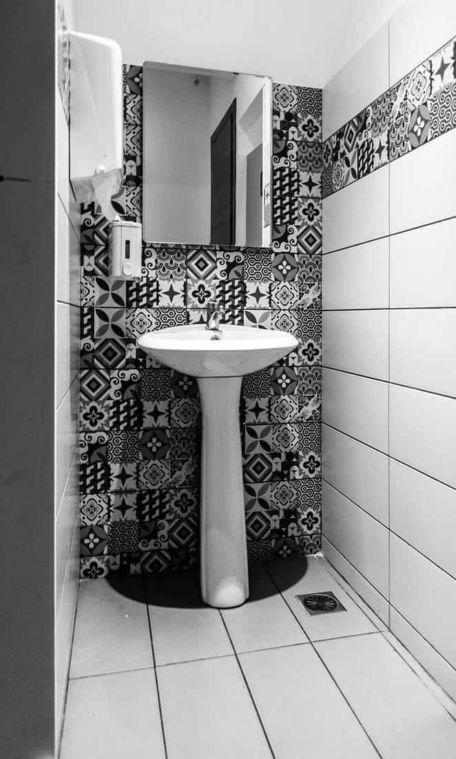 Standing bathroom sink in artistic black and white tiled bathroom